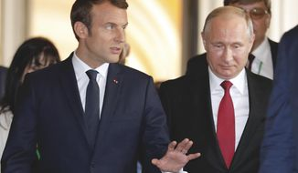 President Emmanuel Macron, left, escorts his Russian counterpart Vladimir Putin as they meet for talks at the Palace of Versailles before the opening of an exhibition marking 300 years of diplomatic ties between the two countries in Versailles, near Paris, France, Monday, May 29, 2017. Monday's meeting comes in the wake of the Group of Seven's summit over the weekend where relations with Russia were part of the agenda, making Macron the first Western leader to speak to Putin after the talks. (Philippe Wojazer/Pool Photo via AP)
