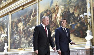 French President Emmanuel Macron, right, speaks to Russian President Vladimir Putin in the Galerie des Batailles (Gallery of Battles) at the Versailles Palace as they arrive for a joint press conference following their meeting in Versailles, near Paris, France, Monday, May 29, 2017. Monday's meeting comes in the wake of the Group of Seven's summit over the weekend where relations with Russia were part of the agenda, making Macron the first Western leader to speak to Putin after the talks. (Stephane de Sakutin/Pool Photo via AP)
