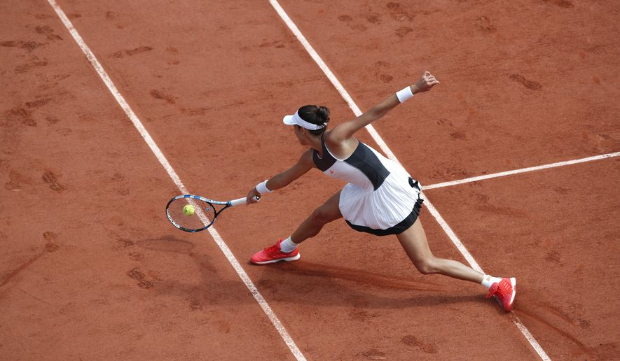 Spain's Garbine Muguruza plays a shot against Italy's Francesca Schiavone during their first round match of the French Open tennis tournament at the Roland Garros stadium, in Paris, France. Monday, May 29, 2017. (AP Photo/Christophe Ena)