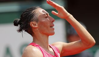 Italy's Francesca Schiavone gestures after missing a shot against Spain's Garbine Muguruza during their first round match of the French Open tennis tournament at the Roland Garros stadium, in Paris, France. Monday, May 29, 2017. (AP Photo/Christophe Ena)