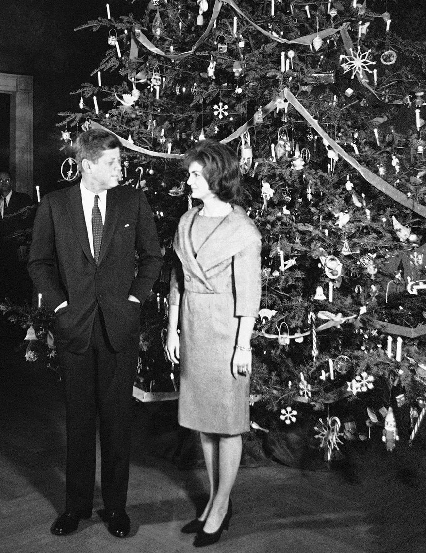 FILE - In this Dec. 13, 1961 file photo, President John F. Kennedy and his wife, Jacqueline, pose in front of the Christmas tree in the Blue Room of the White House in Washington. The occasion was a pre-Christmas party for White House staff members and their families. Monday, May 29, 2017 marks the 100-year anniversary of his birth. (AP Photo/Henry Burroughs)