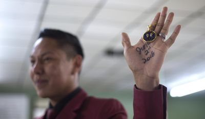 Pernell Manuelito holds up his one year sobriety chip during his speech at Alcoholics Anonymous in Gallup, N.M. (Cayla Nimmo/Gallup Independent via AP)