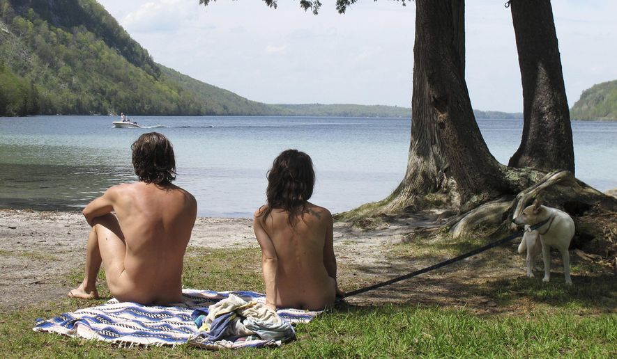 In this Thursday, May 18, 2017 photo, Michael Zarnowski, left, and Katelyn Comeau, of Thornton, N.H., relax at the clothing-optional beach known as the Southwest Cove of Lake Willoughby in Westmore, Vt. Located on state land, state officials said the area, which also includes hiking trails, gets so much use in the summer that upgrades need to be made to protect the area from over use. Beach users are opposed to the plan because they think it could threaten their ability to use the area. (AP Photo/Wilson Ring)