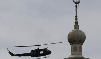 A military helicopter hovers by a mosque as government troops battle with Muslim militants who continue to hold their ground in some areas of Marawi city for almost a week Monday, May 29, 2017 in southern Philippines. Philippine forces control most of the southern city where militants linked to the Islamic State group launched a bloody siege nearly a week ago, authorities said Monday, as the army launched airstrikes and went house-to-house to crush areas of resistance. (AP Photo/Bullit Marquez)