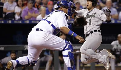 Detroit Tigers' Jose Iglesias (1) beats the tag by Kansas City Royals catcher Salvador Perez to score on a two-run single by Miguel Cabrera during the eighth inning of a baseball game Monday, May 29, 2017, in Kansas City, Mo. (AP Photo/Charlie Riedel)