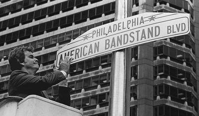 """FILE - In this Oct. 27, 1981, file photo, television personality Dick Clark shines a new sign that changes a portion of Philadelphia's Market Street to American Bandstand Boulevard, to recognize the 30th anniversary of the popular dance program that originated in Philadelphia. Philadelphia has a rich musical legacy: It's birthplace of the lush acoustic style known as The Sound of Philadelphia and the hometown of """"American Bandstand"""" and Chubby Checker's """"Twist."""" But there's no major museum or other place of pilgrimage for music fans that encompasses the city's music history. (AP Photo, File)"""