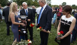 Brittany Jacobs, left, and 8-year-old son Christian Jacobs meet President Donald Trump and Vice President Mike Pence in Section 60 of Arlington National Cemetery, Monday, May 29, 2017, in Arlington, Va. Jacobs father, Marine Sgt. Christopher Jacobs, was killed in 2011. (AP Photo/Evan Vucci)