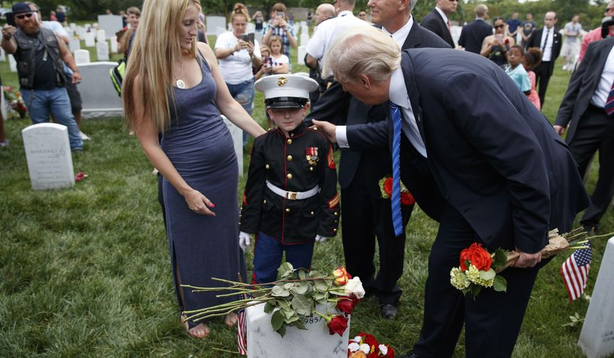 Brittany Jacobs, left, watches as her 8-year-old son Christian Jacobs meets President Donald Trump and Vice President Mike Pence in Section 60 of Arlington National Cemetery, Monday, May 29, 2017, in Arlington, Va. Jacobs father, Marine Sgt. Christopher Jacobs, was killed in 2011. (AP Photo/Evan Vucci)