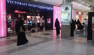 Women and men pass a Victoria's Secret store while in a mall in Jeddah, Saudi Arabia. The kingdom is investing $7 billion to boost tourism and business travel.