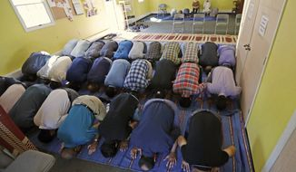 In this Sept. 23, 2016, file photo, Muslim worshippers pray during a service at the Bernards Township Community Center in Basking Ridge, N.J. Bernards Township, N.J., will pay $3.25 million to the Islamic Society of Basking Ridge to settle a lawsuit over the township's denial of a permit to build a mosque, the U.S. Justice Department announced Tuesday, May 30, 2017. Under the settlement, the group will be allowed to build the mosque and the town agreed to limit zoning restrictions placed on houses of worship. (AP Photo/Julio Cortez, File)