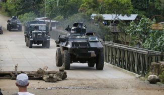 Government troops cross a bridge after securing a village outside Marawi city, Tuesday, May 30, 2017, in the southern Philippines. Muslim militants who attacked Marawi last week, attempted to blow the bridge but was thwarted by villagers. Philippine forces pressed their offensive to drive out militants linked to the Islamic State group after days of fighting left corpses in the streets and hundreds of civilians begging for rescue from a besieged southern city of Marawi. (AP Photo/Bullit Marquez)