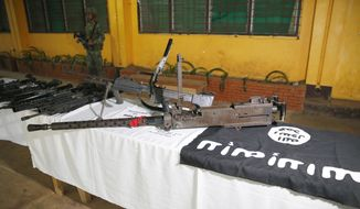 A Philippine Marine guards high-powered firearms, including a 50-caliber machinegun, ammunitions, uniforms, and black ISIS-style flags Tuesday, May 30, 2017 in Marawi city southern Philippines. Philippine forces pressed their offensive to drive out militants linked to the Islamic State group after days of fighting left corpses in the streets and hundreds of civilians begging for rescue from a besieged southern city of Marawi.(AP Photo/Bullit Marquez)
