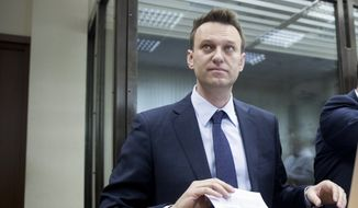 Alexei Navalny holds papers at a court room in Moscow, Russia, Tuesday, May 30, 2017. Hearings have opened in the defamation case between Russian opposition leader Navalny and multi-billionaire Alisher Usmanov. Usmanov, estimated to be worth $15 billion, has sued Navalny over his investigation into Prime Minister Dmitry Medvedev's alleged wealth. (AP Photo/Pavel Golovkin) ** FILE **