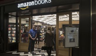 In this Thursday, May 25, 2017, photo, a woman is greeted by an Amazon Books store employee as she arrives at the store in the Time Warner Center at Columbus Circle, in New York. Amazon opened the retail store Thursday. Amazon, the e-commerce giant that changed how people shop for books, toilet paper and TVs, hit a new milestone Tuesday, May 30: Its stock topped $1,000 for the first time. (AP Photo/Mary Altaffer)