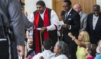Rev. William Barber II, center, president of the North Carolina NAACP, is arrested in front of Sen. Phil Berger's office during a sit-in Tuesday, May 30, 2017. More than thirty people were arrested  inside the state Legislative Building as they protested Republican lawmakers' refusal to expand Medicaid coverage. (Travis Long/The News & Observer via AP)