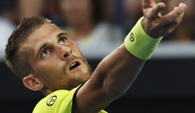 Monday, Jan. 16, 2017 file photo Slovakia's Martin Klizan serves to Switzerland's Stan Wawrinka during their first round match at the Australian Open tennis championships in Melbourne, Australia. French wild card Laurent Lokoli refused a handshake from Martin Klizan of Slovakia Tuesday May 30, 2017, after losing in five sets in the first round of the French Open. Lokoli said he snubbed Klizan because his opponent kept simulating injuries throughout their match, an attitude he said was disrespectful. (AP Photo/Kin Cheung)