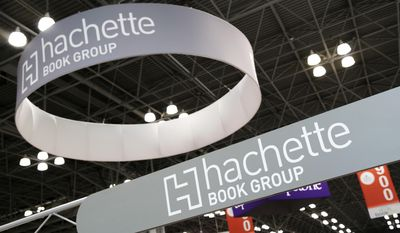 FILE - In this May 28, 2015 file photo, signage for Hachette Book Group are displayed at BookExpo America in New York. Publishers, authors, librarians, and book retailers attend the annual publishing industry show. BookExpo 2017 runs Wednesday thru Friday in New York. (AP Photo/Mark Lennihan, File)