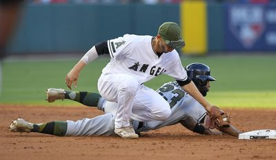Atlanta Braves' Danny Santana, right, is safe as he dives back to second under the tag of Los Angeles Angels shortstop Andrelton Simmons during the third inning of a baseball game, Monday, May 29, 2017, in Anaheim, Calif. (AP Photo/Mark J. Terrill)