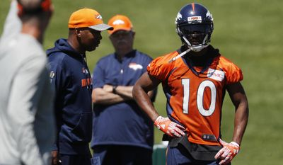 Denver Broncos wide receiver Emmanuel Sanders, back, looks on as offensive coordinator Mike McCoy directs drills during an NFL football minicamp session at the team's headquarters Tuesday, May 30, 2017, in Englewood, Colo. (AP Photo/David Zalubowski)