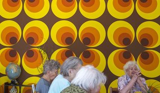 In this May 17, 2017 photo residents sit in front of a colorful wallpaper of the 70s in the Alexa Seniors' Residence in Dresden, eastern Germany. The retirement home has recreated the communist era of the former GDR in two living-rooms to help residents with Alzheimer's and dementia. (AP Photo/Jens Meyer)