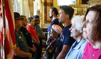 Activists pushing for plans to close so-called corporate tax loopholes and tax the wealthy at higher rates face off with Secretary of State Police at the entrance to the governor's office Tuesday, May 30, 2017 at the Capitol in Springfield, Ill. The protesters are part of a coalition called Fair Economy Illinois. Some members marched from Chicago to Springfield for the final days of the legislative session to urge lawmakers to pass a budget that helps working people. (Rich Saal/The State Journal-Register via AP)