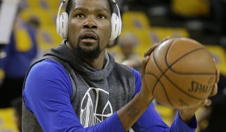 """In this Sunday, May 14, 2017, photo, Golden State Warriors forward Kevin Durant warms up before Game 1 of the NBA basketball Western Conference finals between the Warriors and the San Antonio Spurs in Oakland, Calif. Imagine Kevin Durant as a skinny, timid teen being told to shoot by his middle school point guard who saw so much potential all those years ago. San Francisco 49ers linebacker NaVorro Bowman,the superior player at the time, used to tell tall-and-lanky Durant to be aggressive, to take it to the hoop. """"Can you believe we had to tell him to shoot?"""" Bowman recalled with a grin.  (AP Photo/Jeff Chiu)"""