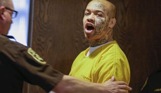 FILE - In this April 16, 2014 file photo, Nikko Jenkins is led to court by a Douglas County deputy in Omaha, Neb. Jenkins, convicted of killing four people in and around Omaha in 2013, has been sentenced to execution or life in prison. A three-judge panel will announce on Tuesday, May 30, 2017, whether Jenkins is sentenced to death or to life in prison. Jenkins' sentencing has been delayed several times because of questions about his competency.  (AP Photo/Nati Harnik, File)