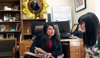 In this May 18, 2017, photo, Oregon Rep. Teresa Alonso Leon, left, speaks with her legislative aide, Audrey Mechling, in Alonso's office in the Oregon State Capitol in Salem, Ore. Alonso is Oregon Legislature's first Latina immigrant lawmaker. (AP Photo/Andrew Selsky)