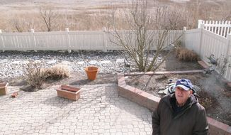 In this Feb. 16, 2017 photo Marty Mozzo poses in his backyard in Ocean City N.J. on the edge of a back bay wetlands. When he and his wife were considering buying the house, they looked at a small trickle of water in the distance and wondered if the property would flood, deciding the water was too far away to pose a danger. Within weeks, their house was surrounded by floodwaters. (AP Photo/Wayne Parry)