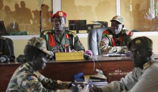 The judges sit in the courtroom during the trial of South Sudanese soldiers accused of an attack during the country's civil war, in the capital Juba, South Sudan Tuesday May 30, 2017. South Sudanese soldiers accused of a horrific attack on foreign aid workers during the country's civil war are facing trial almost a year later. Twelve of the 20 soldiers accused of rape, torture, killing and looting during the attack on the Terrain hotel compound were in court Tuesday. The trial is a test of South Sudan's ability to hold its soldiers accountable. (AP Photo/Bullen Chol).