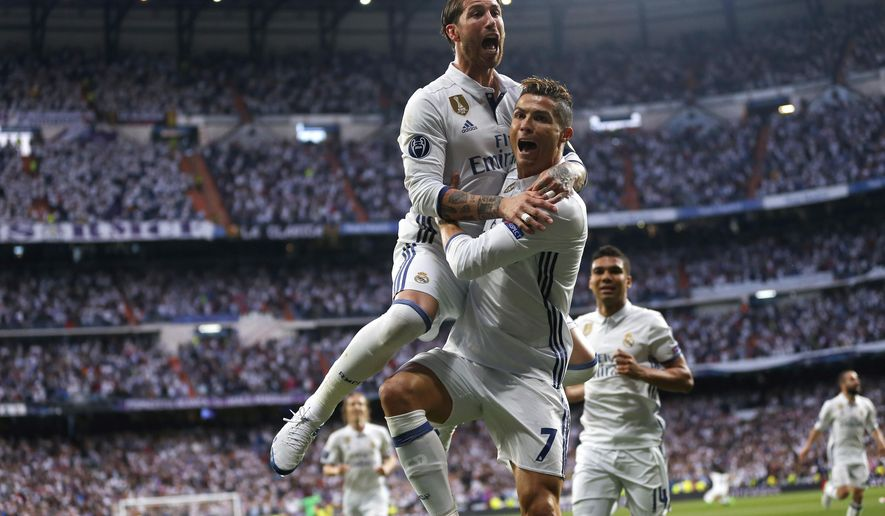 FILE - In this May 2, 2017 file photo, Real Madrid's Cristiano Ronaldo, celebrates with Real Madrid's Sergio Ramos, left, after scoring the opening goal during the Champions League semifinals first leg soccer match against Atletico Madrid at Santiago Bernabeu stadium in Madrid, Spain. Real Madrid meet Juventus in the Champions League final in Cardiff on Saturday June 3, 2017. (AP Photo/Daniel Ochoa de Olza, File)