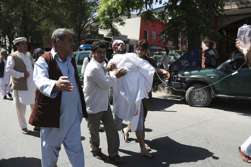People carry an injured man after a suicide attack in Kabul, Afghanistan, Wednesday, May 31, 2017. A massive explosion rocked a highly secure diplomatic area of Kabul on Wednesday morning, causing casualties and sending a huge plume of smoke over the Afghan capital. (AP Photos/Rahmat Gul)