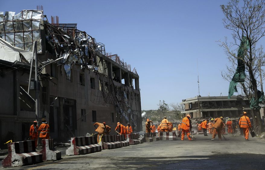 Afghan Municipality workers sweep a road in front of German Embassy after a suicide attack in Kabul, Afghanistan, Wednesday, May 31, 2017. A massive explosion rocked a highly secure diplomatic area of Kabul on Wednesday morning, causing a big number of casualties and sending a huge plume of smoke over the Afghan capital. (AP Photos/Rahmat Gul)