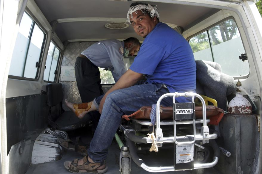 A wounded cameraman from 1TV channel, a local TV channel, receives some assistance near the site of a suicide attack in Kabul, Afghanistan, Wednesday, May 31, 2017. A massive explosion rocked a highly secure diplomatic area of Kabul on Wednesday morning, causing casualties and sending a huge plume of smoke over the Afghan capital. (AP Photos/Massoud Hossaini)