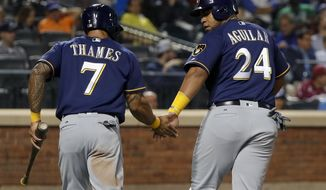 Milwaukee Brewers Jesus Aguilar (24) greets Eric Thames (7) after the two scored on a base hit by Hernan Perez against the New York Mets during the fourth inning of a baseball game, Wednesday, May 31, 2017, in New York. (AP Photo/Julie Jacobson)