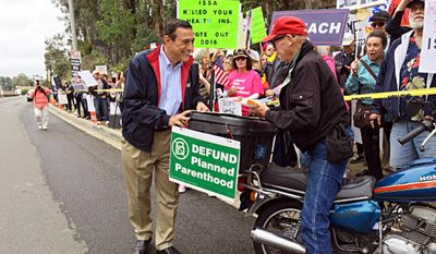 This photo provided by the Office of Rep. Darrell Issa (R-Calif.) shows the congressman meeting with demonstrators, both pro and con, across the street from his office in Vista, Calif., Tuesday, May 30, 2017. (Office of Rep. Darrell Issa via AP)