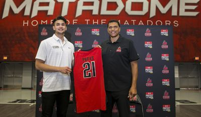 Cal State Northridge basketball coach Reggie Theus, right, introduces Kobe Paras in Northridge, Calif., Wednesday, May 31, 2017. Paras has transferred from Creighton to Northridge and will be eligible to play basketball for the Matadors in 2018-19. The 6-foot-6 guard from Manila, Philippines, returns to Los Angeles, where he played at Cathedral High before transferring to Middlebrooks Academy for his senior year. (AP Photo/Damian Dovarganes)