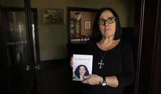 In this May 12, 2017, photo, Bobbie Jo Lowe holds a DVD with a photo of her daughter Alexis Kohlman, in her Port Clinton, Ohio, home. After Kohlman died in January from an infection caused by drug abuse, Lowe decided to open the first women's recovery home in Port Clinton. The home, called Alexis House, will help women struggling with addiction reintegrate into society. (Andy Morrison/The Blade via AP)