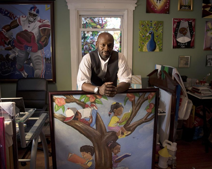 Artist Chris Fabor Muhammad in his studio at his home in Paterson, N.J., with a piece the Paterson Library is considering putting on display on Wednesday, May 24, 2017.   (Michael Karas/The Record via AP)