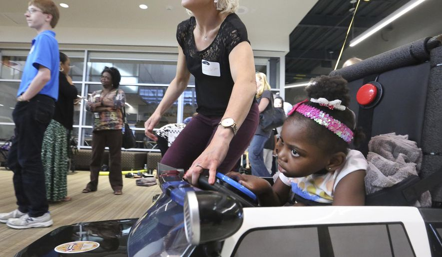 ADVANCE FOR USE MONDAY, JUNE 5 - In this Wednesday, May 24, 2017 photo, Angie Ngoma, 6, takes a tour in her customized car with the help of Maggie Krueger, physical therapist with Frisco ISD, as special needs children enjoy driving motorized ride-on toy cars retrofitted by Frisco schools engineering students at the Frisco ISD Career and Technical Education Center in Frisco, Texas. (Louis DeLuca/The Dallas Morning News via AP)