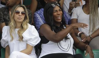 Serena Williams of the U.S., center, watches her sister Venus Williams' match against Japan's Kurumi Nara during their second round match of the French Open tennis tournament at the Roland Garros stadium, in Paris, France. Wednesday, May 31, 2017. (AP Photo/Petr David Josek)
