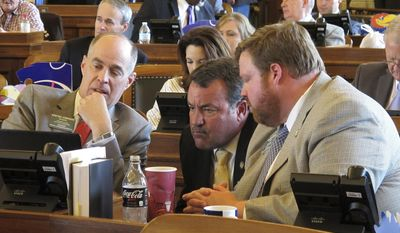 Kansas House Taxation Committee Chairman Steven Johnson, left, R-Assaria, confers with Reps. Kent Thompson, R-Iola, and Blaine Finch, right, R-Ottawa, during the House's session, Wednesday, May 31, 2017, at the Statehouse in Topeka, Kan. Johnson has been negotiation with senators over tax issues but lawmakers are having trouble agreeing on revenue-raising proposals. (AP Photo/John Hanna)