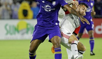 Orlando City's Cyle Larin, front left, battles for possession of the ball with D.C. United's Luciano Acosta, during the first half of an MLS soccer game, Wednesday, May 31, 2017, in Orlando, Fla. (AP Photo/John Raoux)