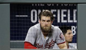 In this Friday, May 19, 2017, photo, Washington Nationals' Bryce Harper sits in the dugout in the fifth inning of a baseball game against the Atlanta Braves in Atlanta. San Francisco Giants reliever Hunter Strickland has received a six-game suspension and Harper four games for their roles in a benches-clearing brawl at AT&T Park on Monday, May 29. (AP Photo/David Goldman)