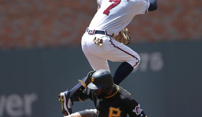 FILE - In this Thursday, May 25, 2017, file photo, Atlanta Braves shortstop Dansby Swanson (7) avoids Pittsburgh Pirates' Josh Harrison (5) as he turns a double play on a Josh Bell ground ball in the first inning of a baseball game in Atlanta. Los Angeles Angels' Mike Trout has ever been concerned about his safety when stealing a base, it hasn't held him back. For him and many of baseball's best baserunners, it might not matter anyway. Harrison recently tested the bounds of his knee ligaments with a wild slide to avoid a tag at second base. (AP Photo/John Bazemore, File)