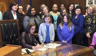Gov. Kate Brown, seated, signs House Bill 2673 in Salem, Ore., Wednesday, May 31, 2017, making the process more private for transgender individuals to change their birth certificate records. The new law makes Oregon the second state with an alternative option for transgender people to update their birth records. (AP Photo/Kristena Hansen)