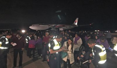 Police take statements for passengers evacuated from a Malaysia Airlines plane after a man tried to enter its cockpit in Melbourne, Australia, Thursday, June 1, 2017. The Malaysia Airlines plane returned to Australia after the man threatened to detonate a bomb and attempted to enter the cockpit before he was tackled and tied up by passengers, police said Thursday. The 25-year-old Sri Lankan man had been discharged from a Melbourne psychiatric hospital on Wednesday before buying a ticket on the late-night flight to Kuala Lumpur, Malaysia. (Andrew Leconcelli via AP)