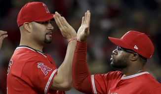 Los Angeles Angels' Albert Pujols, left, celebrates with Eric Young Jr. after the team's 2-1 win against the Atlanta Braves in a baseball game in Anaheim, Calif., Wednesday, May 31, 2017. (AP Photo/Chris Carlson)