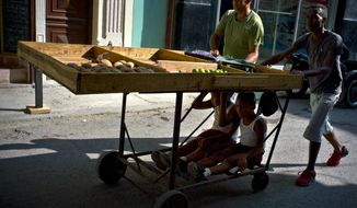 Fruit and vegetable vendors push their cart after a day's work, as two boys ride under the cart in Havana, Cuba, Wednesday, May 31, 2017.  The number of officially self-employed Cubans has grown by a factor of five since President Raul Castro launched limited market-based reforms in 2010. (AP Photo/Ramon Espinosa)