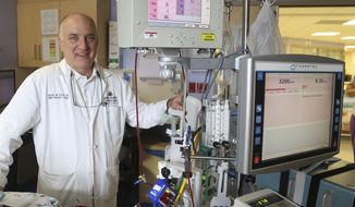 ADVANCE FOR USE SUNDAY, JUNE 4 - In this Monday, May 29, 2017 photo, Dr. David Kays, of Johns Hopkins All Children's Hospital in St. Petersburg, Fla., poses with an extracorporeal membrane oxygenation (ECMO) machine in the hospital's cardiovascular intensive care unit. Sage McCue, 11, of Palmetto, Fla., recently returned home from the hospital, after a near-four-month stay. In January, Sage went to see a doctor over a stuffy nose but was put on a life-saving ECMO machine for more than two months when doctors discovered she had pneumonia and the flu.  (Scott Keeler/Tampa Bay Times via AP)